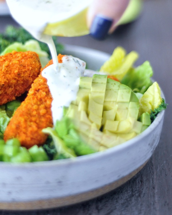 Vegan Buffalo Wing Salad in a a bowl, ranch dressing poured over