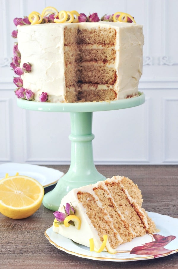 Lemon Elderflower Layer Cake on light green cake stand; one slice cut from it showing inside layers, slice on plate in front of cake stand
