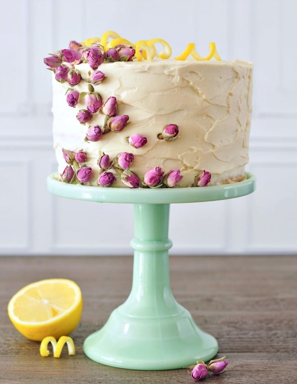 Lemon Elderflower Layer Cake on a light green cake stand, cake garnished with pink edible dried flowers and yellow lemon peel curls