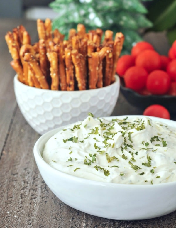 vegan Herb Cheese spread in a white ceramic serving bowl, pretzels and vegetables for dipping