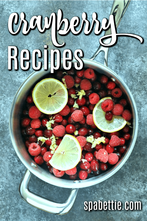 fresh cranberries in a pot with raspberries, minced ginger and lemon slices