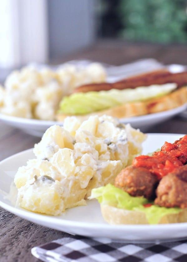 Best Potluck Recipe - Egg Free Potato Salad served alongside potluck items: hot dogs, greens, hot sauce