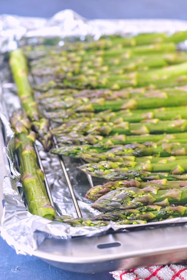 How To Roast Asparagus (photo of fresh asparagus arranged in a single layer on a baking sheet)