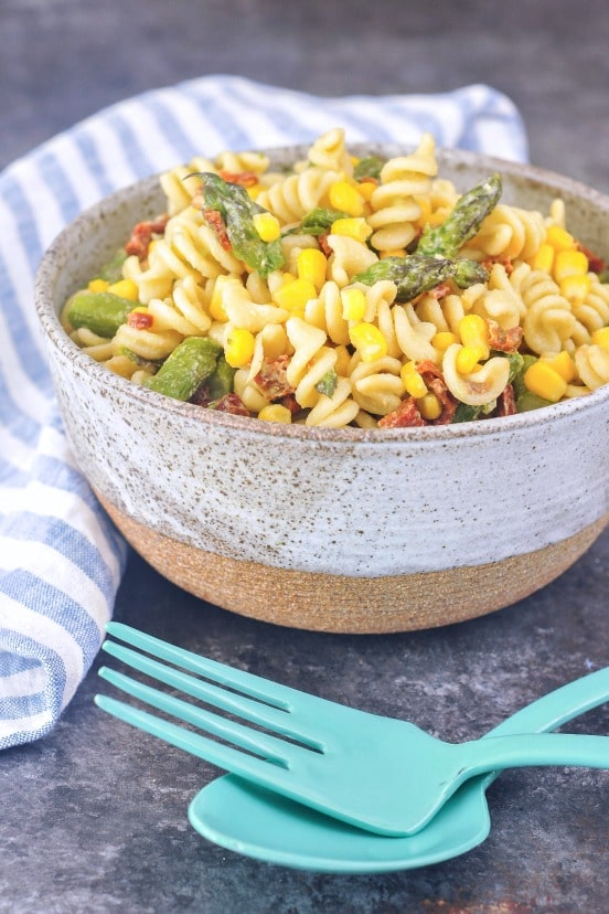 Picnic Pasta Salad in a large rustic bowl with bright blue serving utensils: curly pasta, asparagus, corn, sundried tomatoes