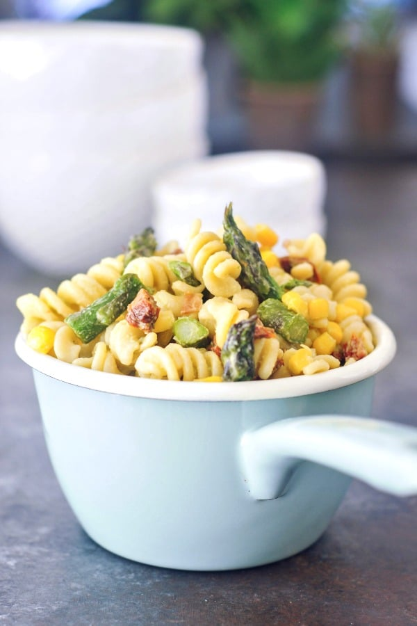 Vegan Pasta Salad (serving dish of corkscrew pasta with sliced asparagus, fresh corn kernels, sundried tomatoes, avocado dressing)