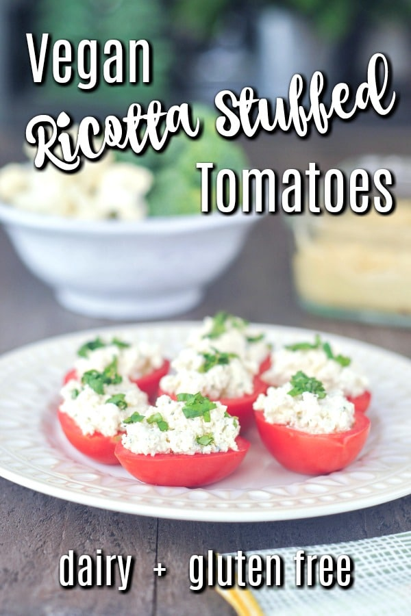 Vegan Ricotta Stuffed Tomatoes topped with fresh chopped basil, sitting on a plate with other appetizer dishes in background
