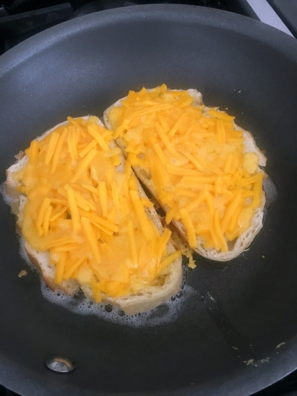 How To Make A Jalapeno Popper Sandwich: slices of bread in a buttered skillet, topped with grated cheese