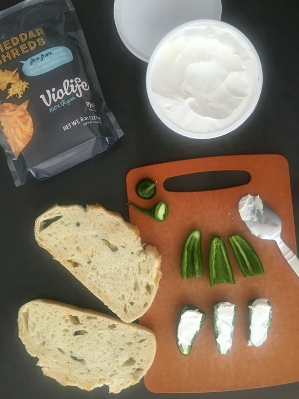 How To Make A Jalapeno Popper Sandwich: slices of bread, cream cheese filled jalapenos, shredded cheese on a cutting board