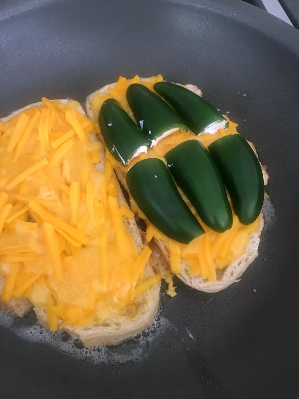 How To Make Jalapeno Popper Grilled Cheese: slices of bread in a buttered skillet, topped with melting cheese and jalapeno poppers