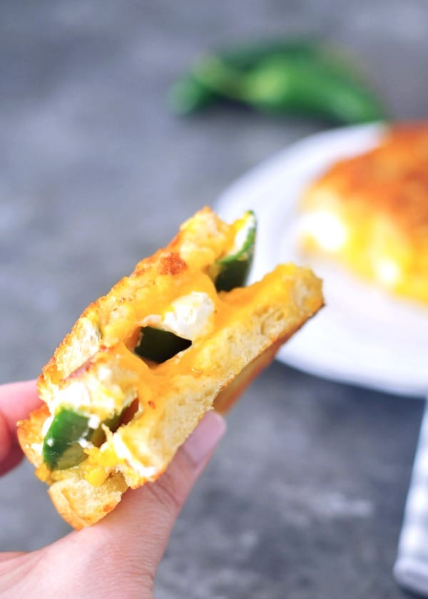 Jalapeno Popper Grilled Cheese held in a hand, other half of sandwich on plate in background