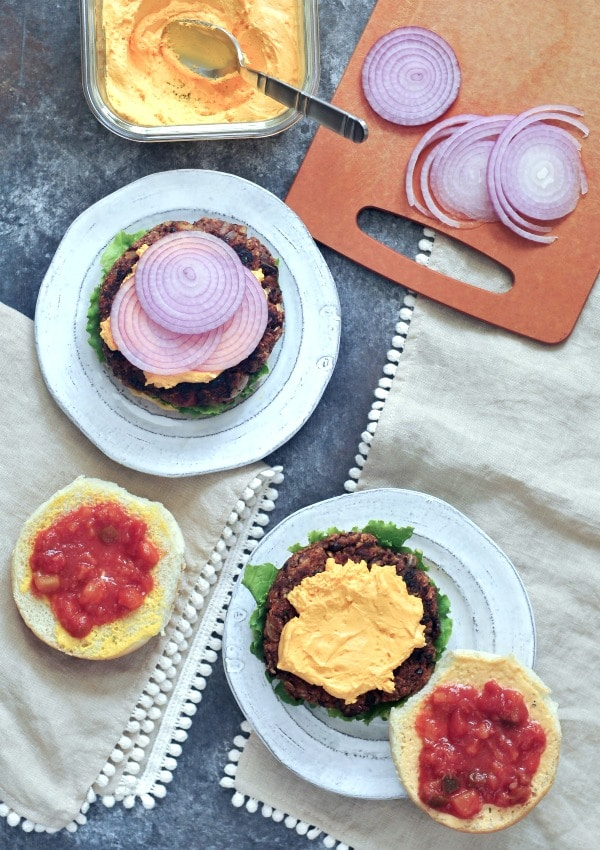 Southwest Veggie Burger - overhead view of burgers on plates with buns and various toppings. cutting board with sliced red onion, glass container of bright yellow cheese sauce, red salsa on top buns