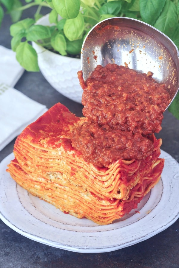 Small Batch Lasagna: slice with meat sauce being poured over top