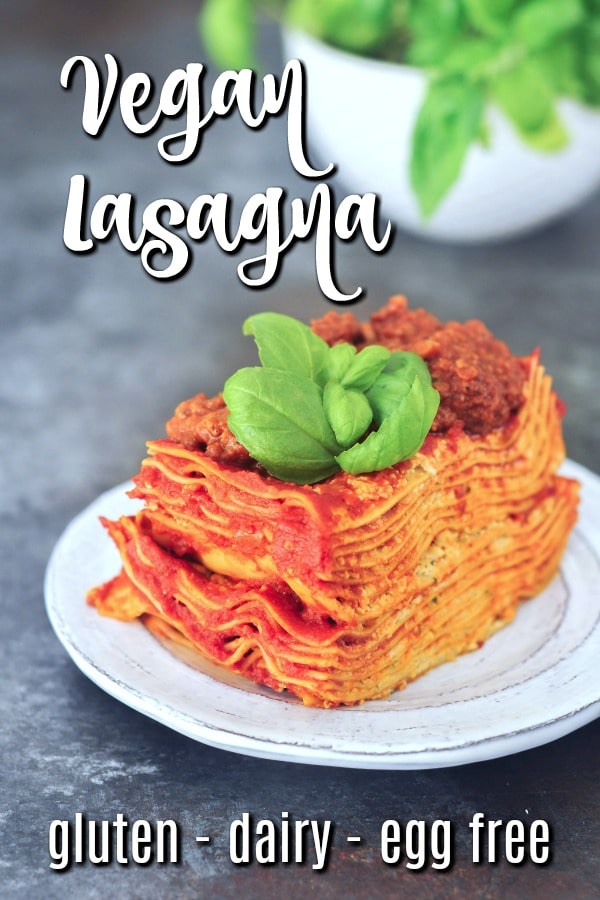 tall slice of Vegan Lasagna on a dish with fresh basil, full plant of basil in background