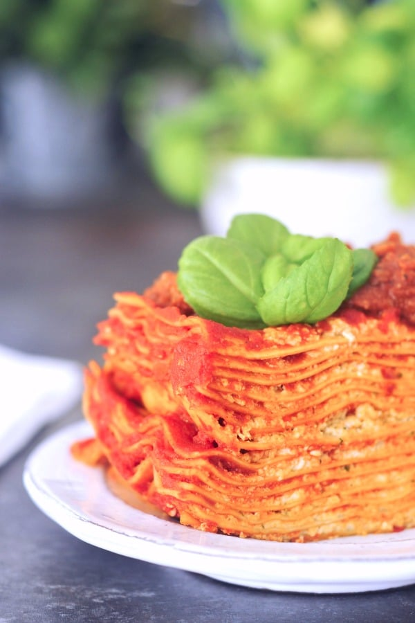 gluten free Vegan Lasagna Recipe: one 12 layer stack of lasagna on a plate, basil plant in background
