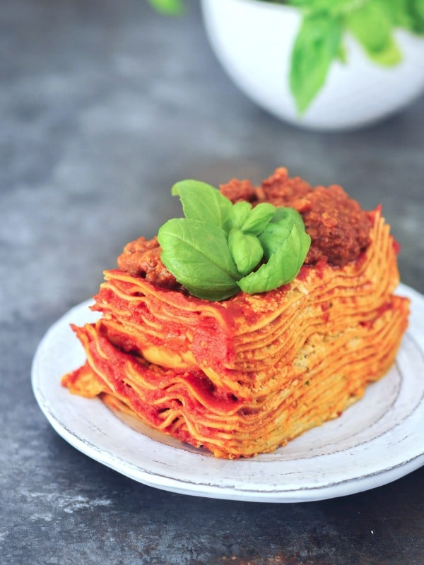 twelve layer slice of gluten free Vegan Lasagna on a rustic plate, garnished with fresh basil
