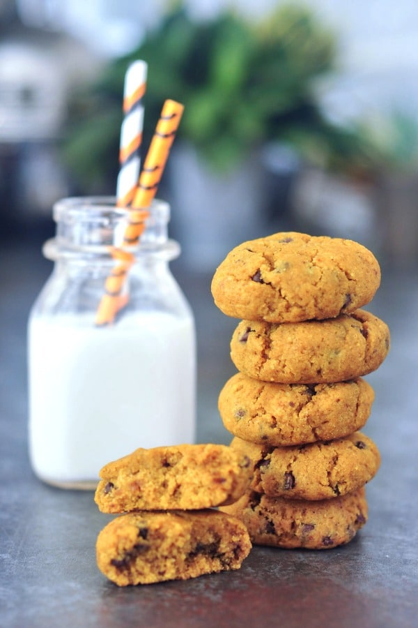 soft pumpkin cookies in a stack, next to a short bottle of almond milk with striped straws