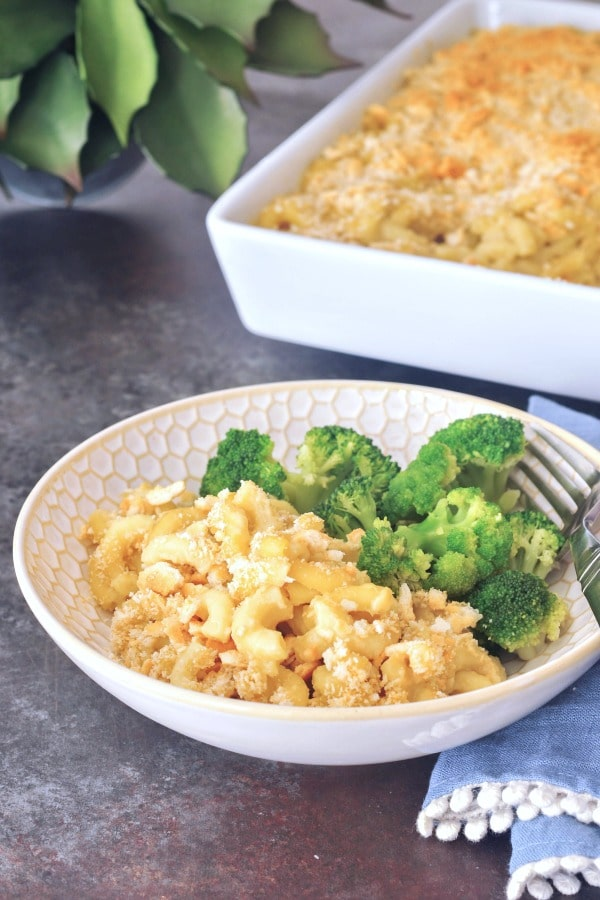 bowl of vegan baked mac and cheese with broccoli on the side, full baking dish of mac and cheese in background