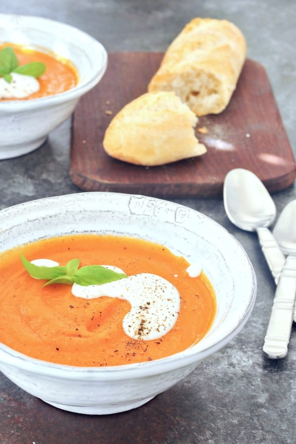 soup in a bowl, topped with cashew cream and fresh basil