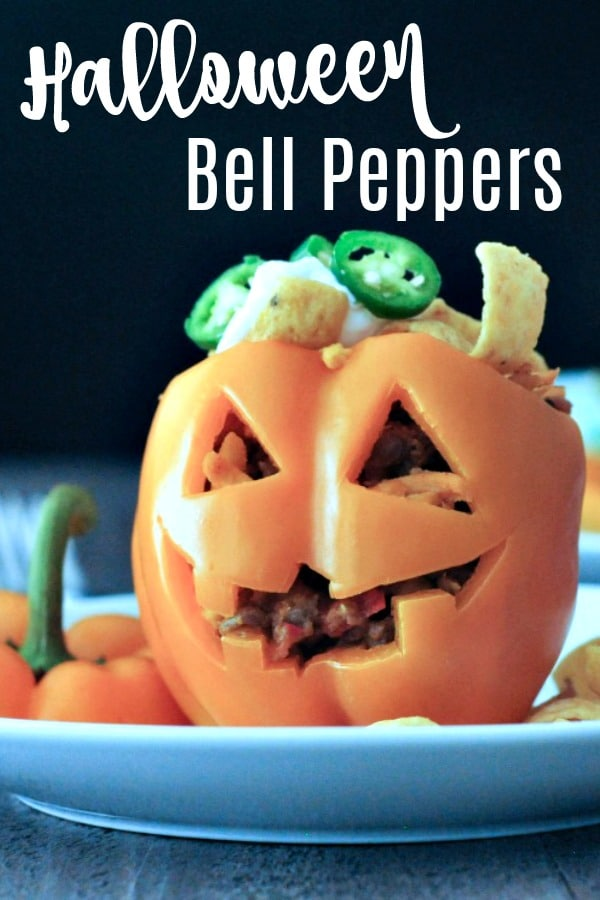 orange bell pepper carved into a jack o lantern, filled with Frito Pie
