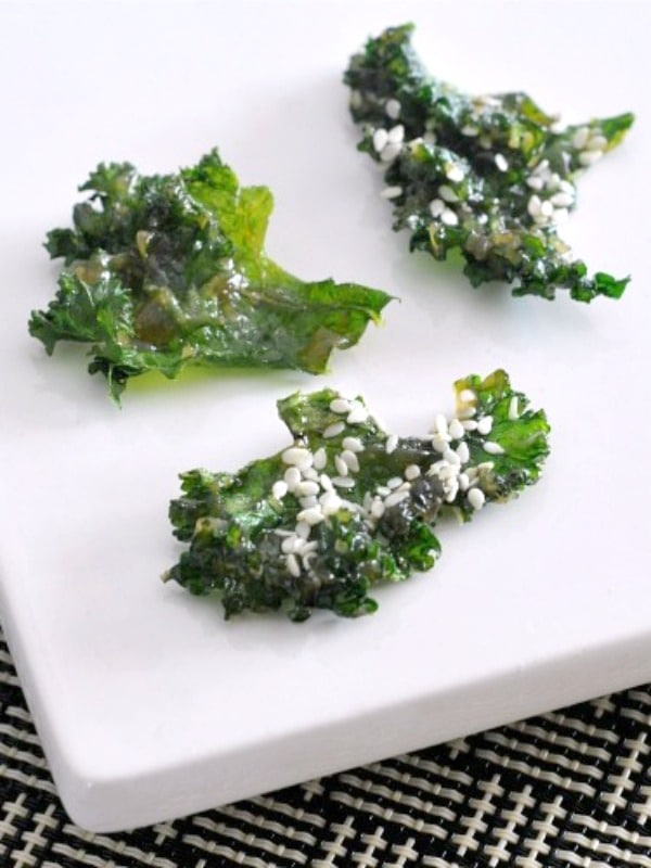 bright green crispy kale chips with miso and sesame seeds on a white plate