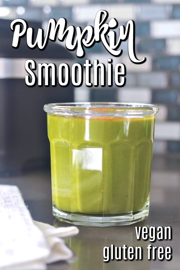 green pumpkin smoothie in a glass, blender in background