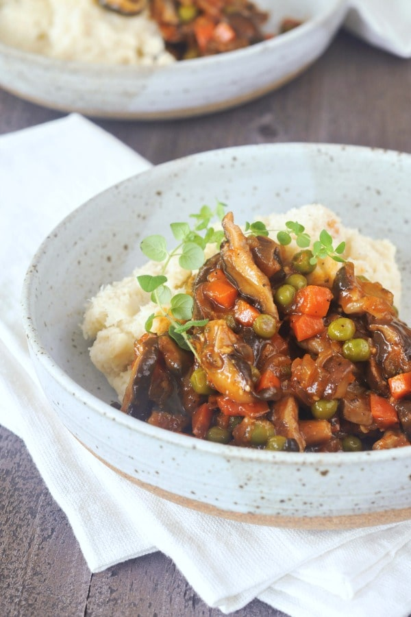 bowl of mushroom stew served over mashed cauliflower, sprig of fresh green thyme on top