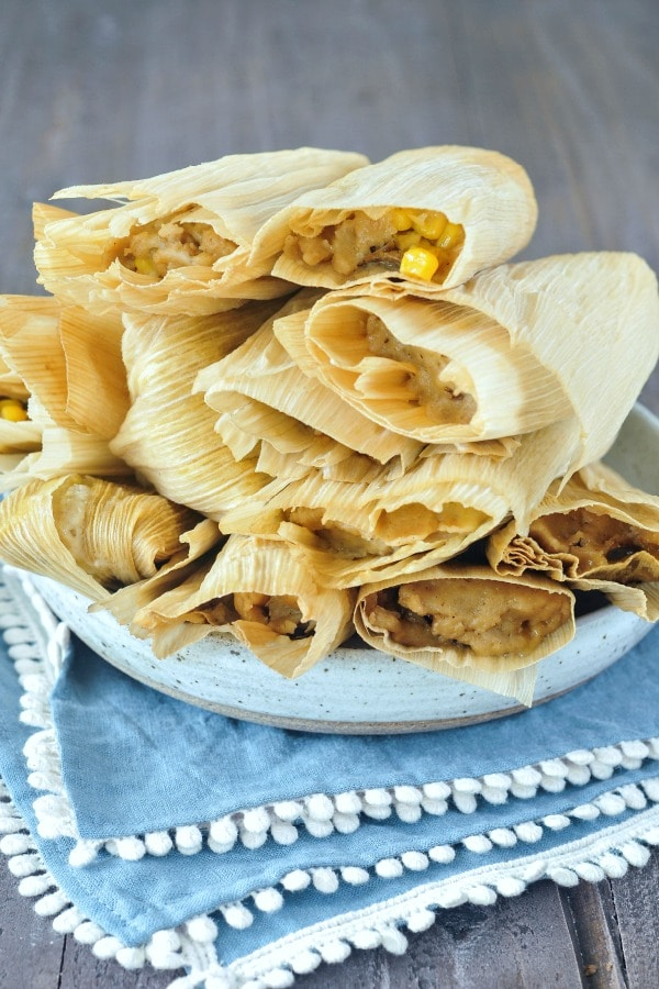 a plate of steamed vegan tamales wrapped in corn husks, stacked high