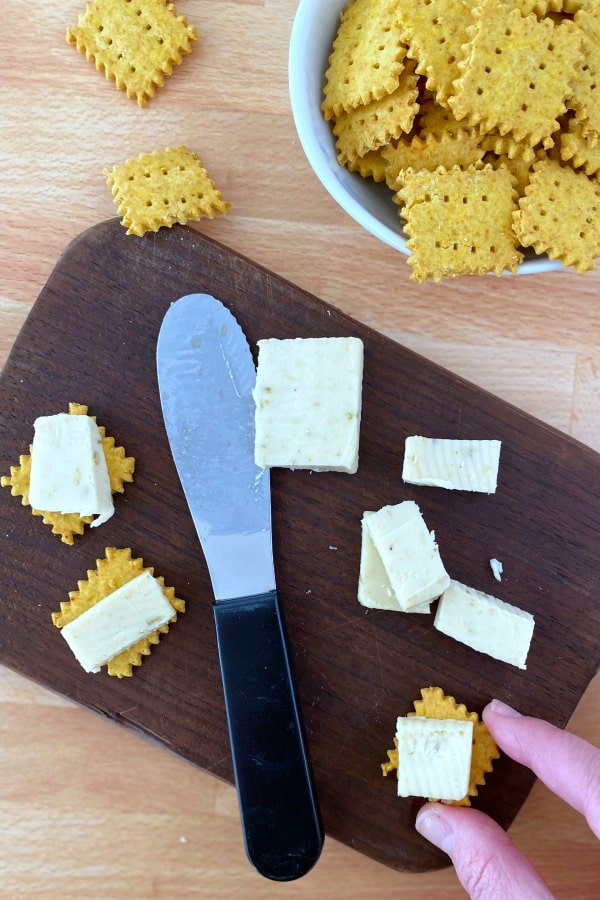 a board with vegan cheese crackers, cheese, and a knife