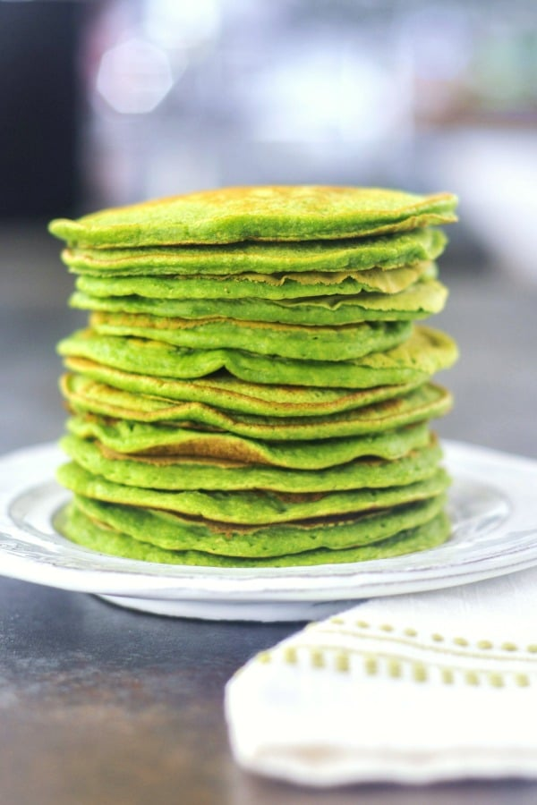 a stack of green pancakes on a white rustic plate.