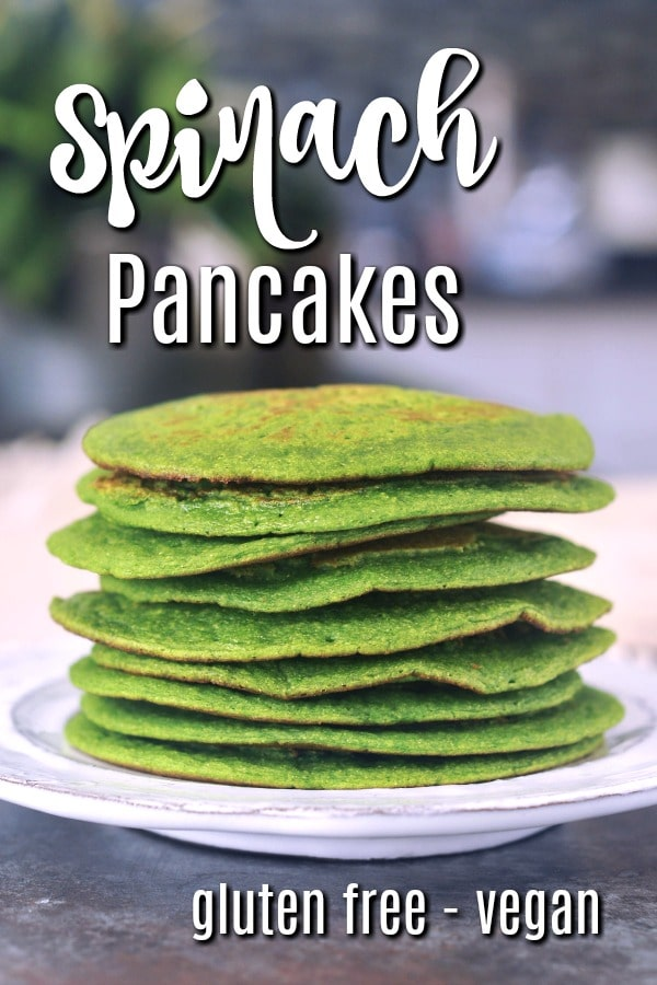 a stack of bright green spinach pancakes on a white rustic plate.