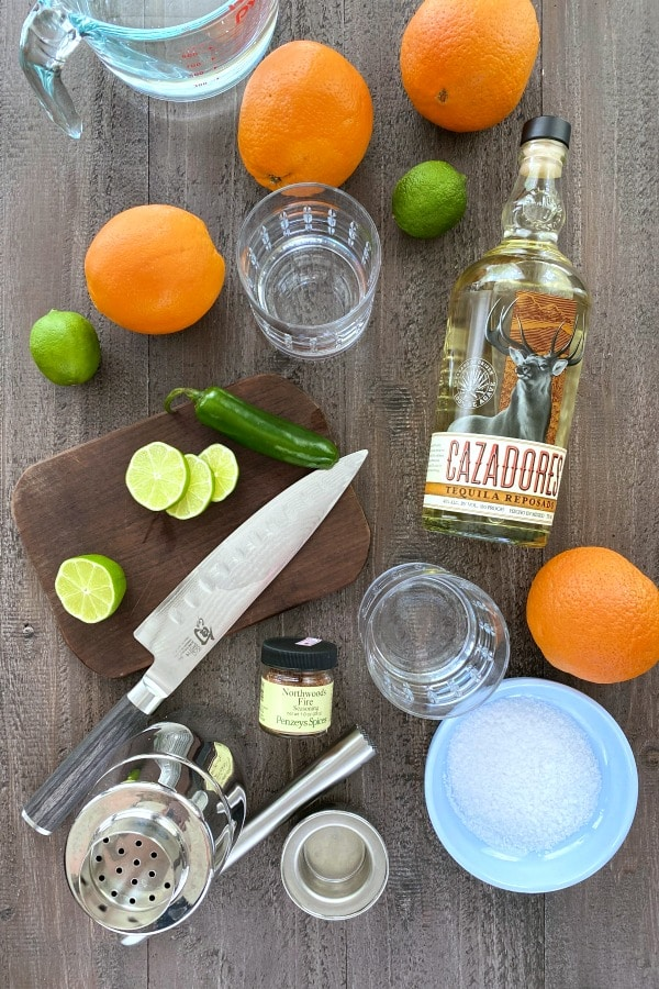 ingredients for making a margarita: fresh oranges, limes, and jalapeno, tequila, salt, soda