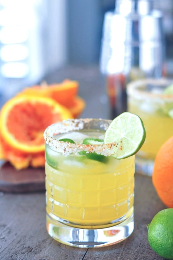 a jalapeno margarita in a rocks glass with a salted rim. orange and lime on the side.