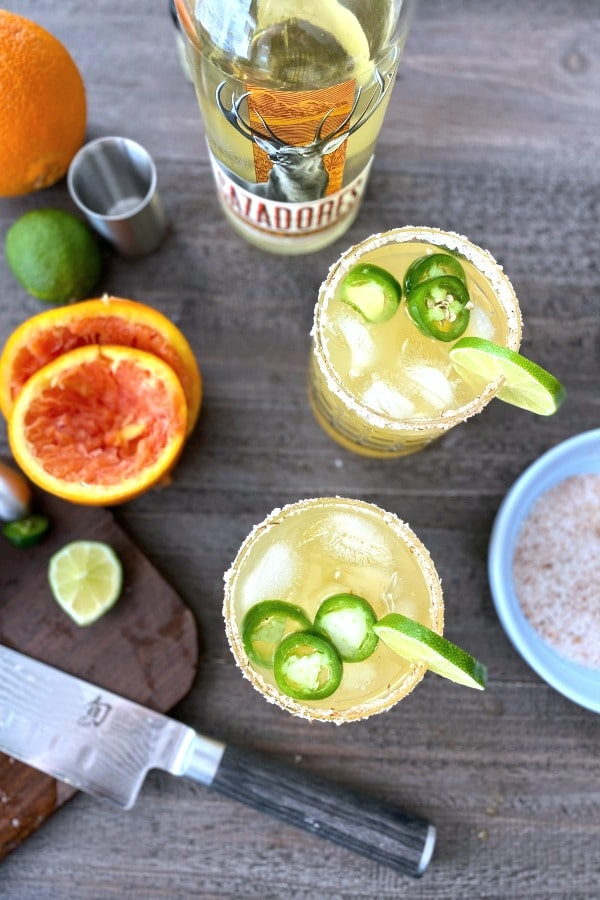 overhead view of jalapeno margaritas, with juiced orange rinds and sliced lime on the side.