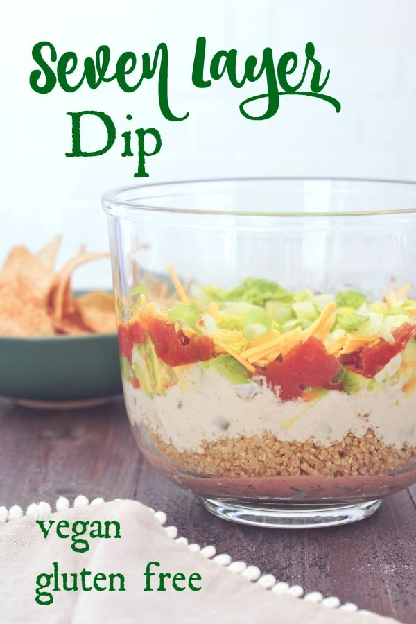 side view of all the layers in seven layer dip: beans, quinoa, cashew cheese sauce, avocado, tomato, green onions and lettuce