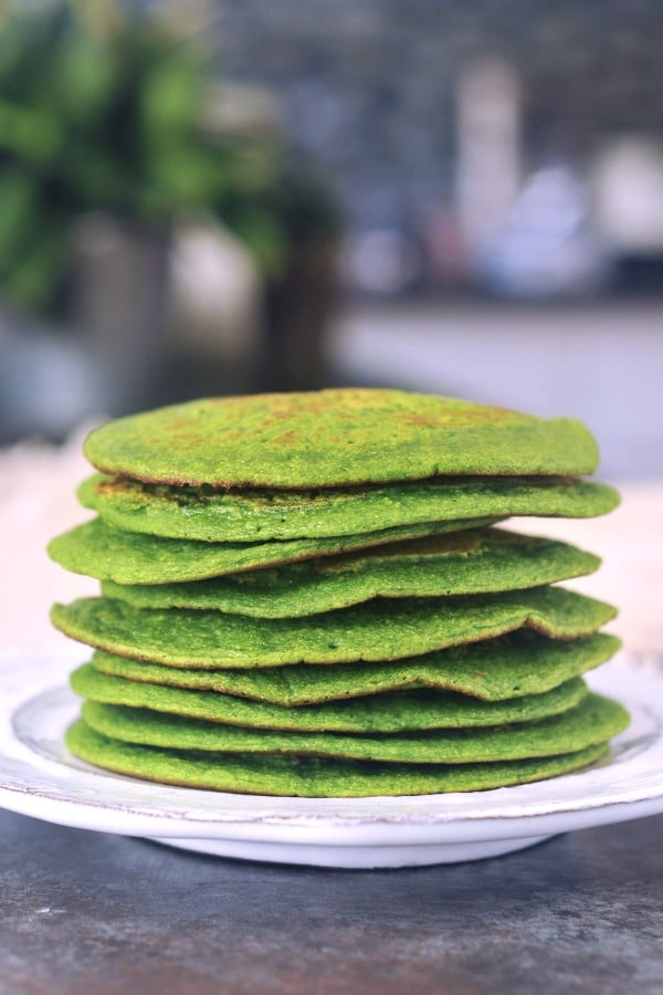 a stack of green spinach pancakes on a white rustic plate.