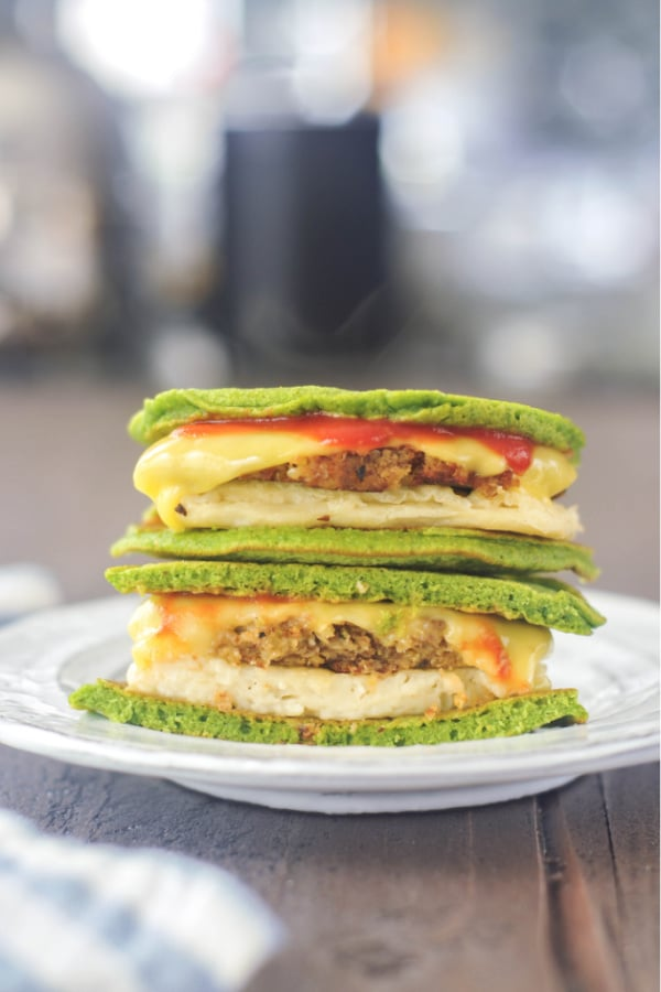 a breakfast sandwich using green vegan spinach pancakes as bread. sliced in half and stacked on a plate to show filling: vegan egg, sausage, melted cheese, ketchup between bright green pancakes.