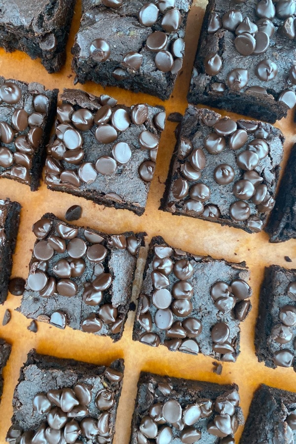 overhead image of sweet potato brownies topped with chocolate chips, cut into squares on a cutting board