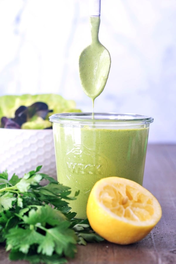 a jar of Green Goddess dressing with a spoon coming out of it, a squeezed lemon and a bunch of herbs on the side.