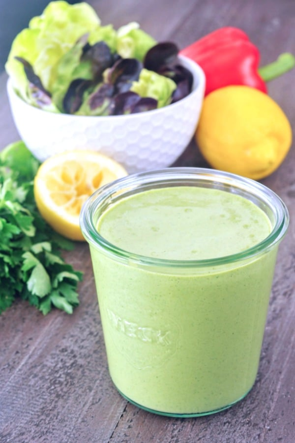 a jar of Green Goddess dressing in front of a salad bowl of greens. a squeezed lemon, a red bell pepper, and a bunch of fresh herbs in background.