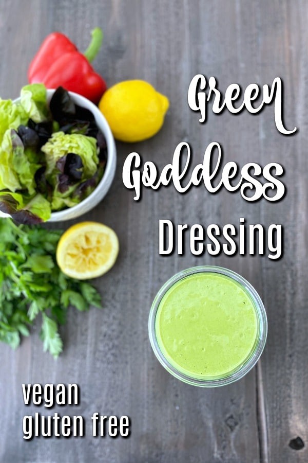 overhead photo of a jar of Green Goddess dressing and a salad bowl of greens. a squeezed lemon, a red bell pepper, and a bunch of fresh herbs in background.