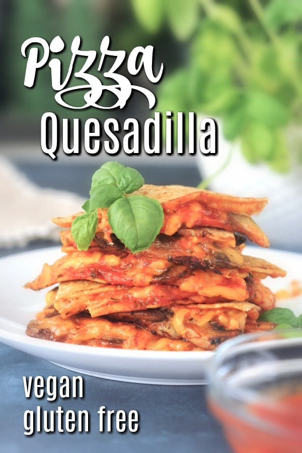 a stack of pizza flavored quesadilla slices on a white plate, fresh basil leaves on top