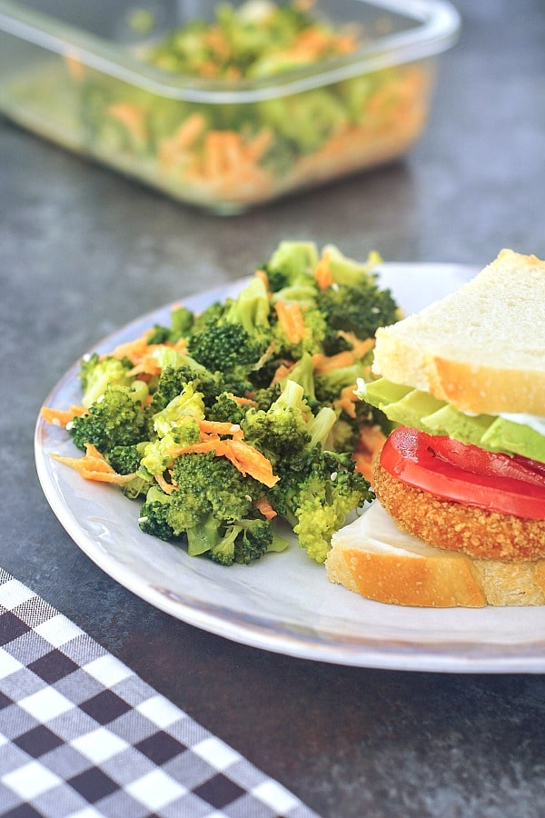 a photo in a broccoli salad recipe: a plate with a sandwich and broccoli salad, glass food storage container of broccoli salad in background.