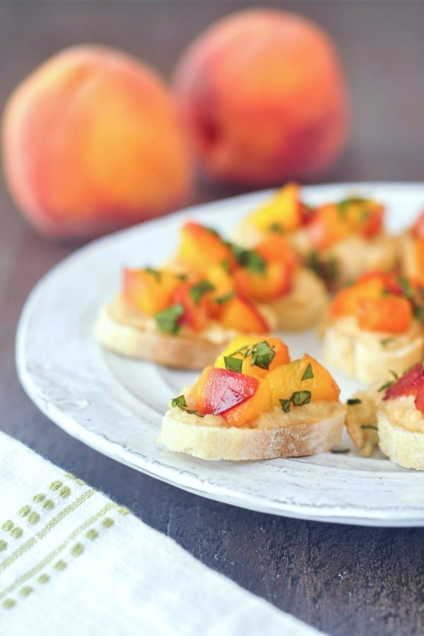 rustic plate with sweet cream peach crostini topped with chopped basil leaves, two fresh peaches in background