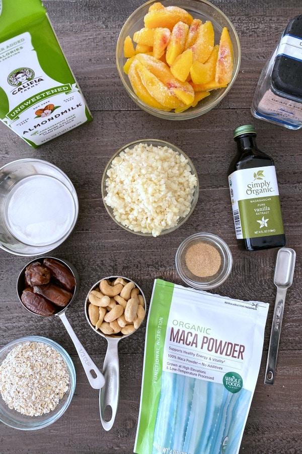 overhead view of ingredients in a peach smoothie: almond milk, peaches, frozen cauliflower, dates, cashews, oats...