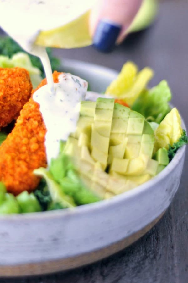 ranch dressing poured over a salad with greens, diced avocado, celery, and buffalo wings