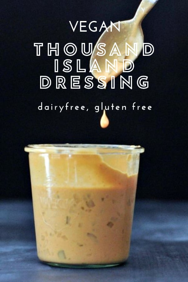 a large glass jar of vegan thousand island dressing, with a spoon dripping sauce above the jar. black background.