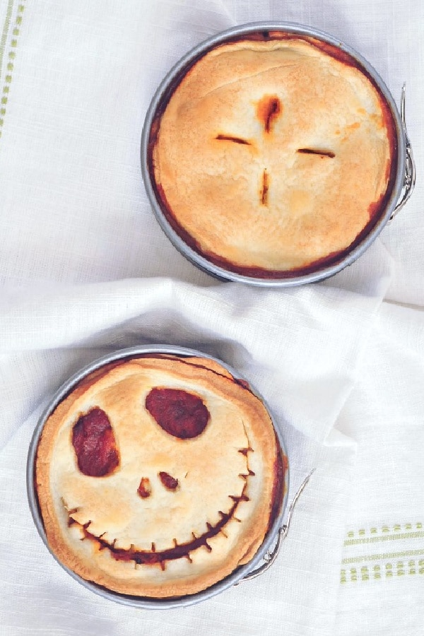 an overhead view of two mini pizza pot pies in springform pans, one pie crust vented with four slits in a clover pattern, the other pie crust cut into a Jack Skellington skeleton face