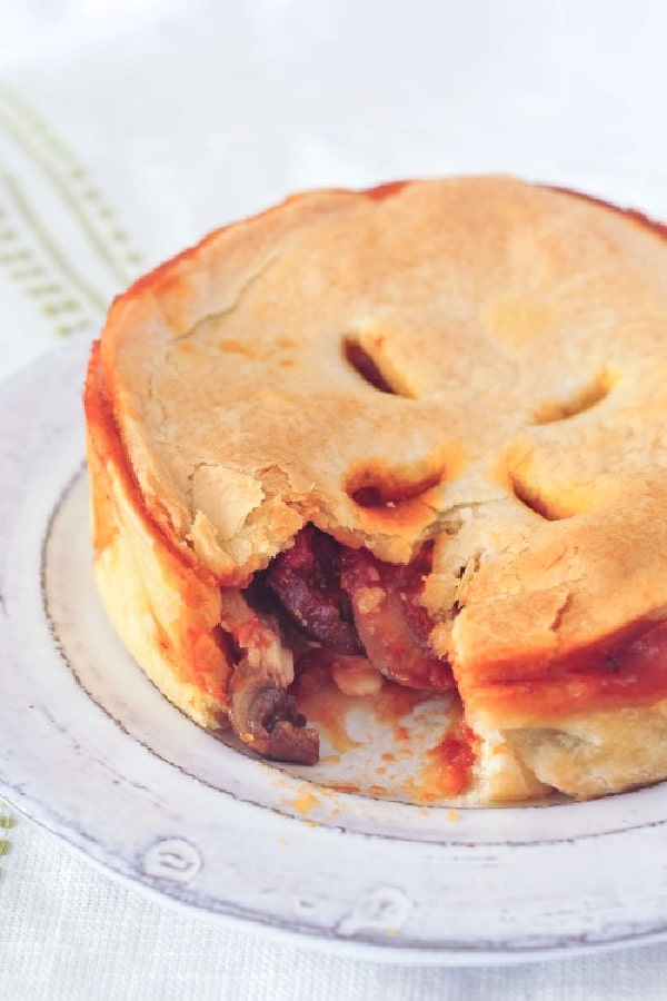 a mini deep dish pizza pot pie on a dish, one bite removed to show filling of mushrooms, sauce, cheese