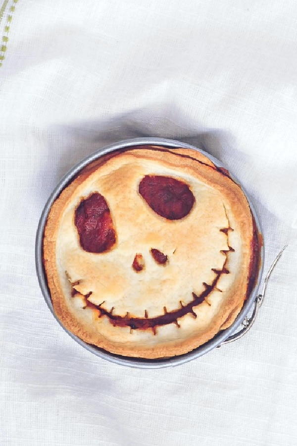 an overhead view of a mini pizza pot pie in a springform pan, the top of the pie cut into a Jack Skellington skeleton face