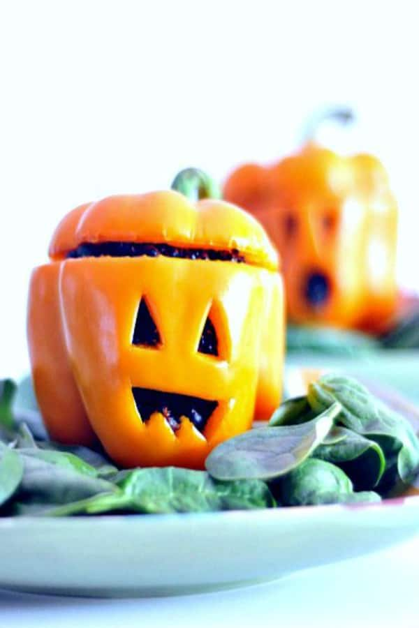 orange bell peppers carved to look like Halloween jack o lanterns, stuffed with black beans and black quinoa, served on a plate over fresh spinach salad